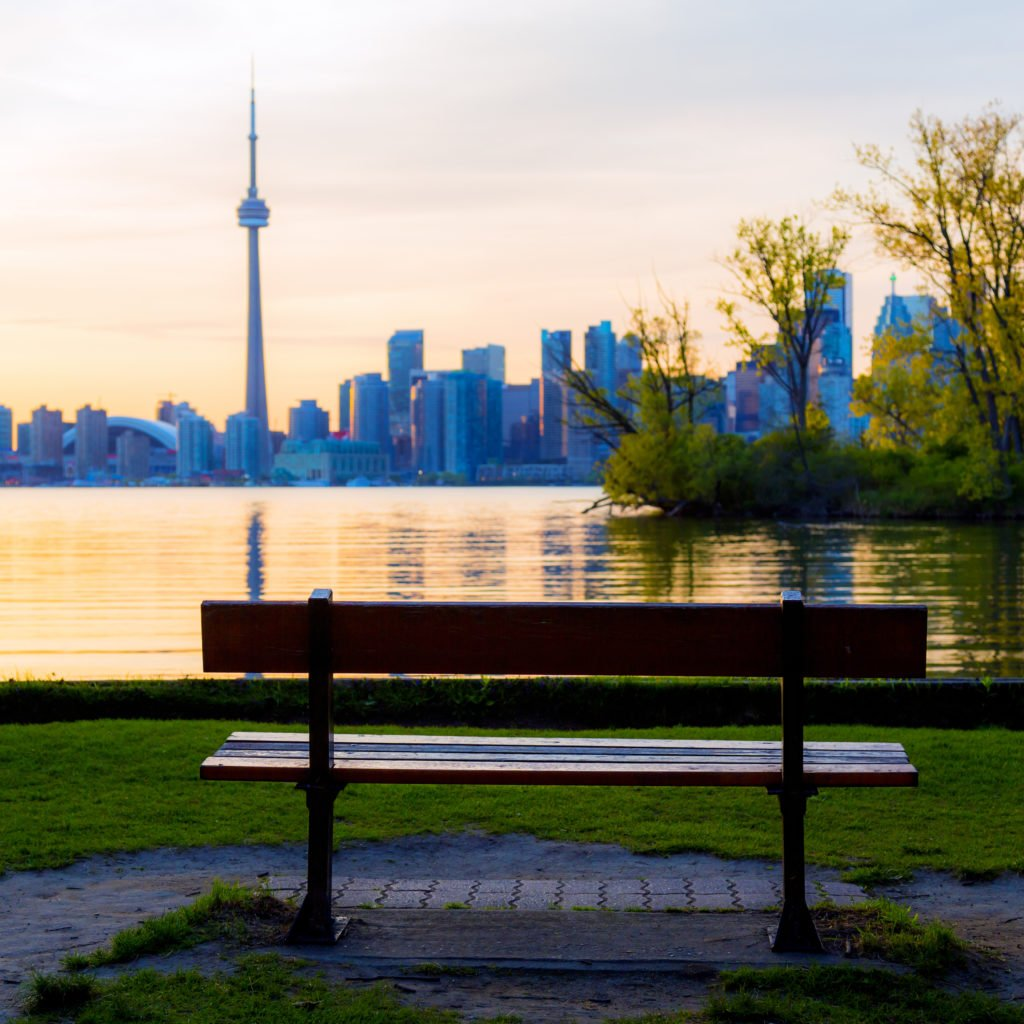Bench On Ward's Island With Toronto Cityscape With CN Tower And Baseball Stadium At Dusk, Ontario, Canada.