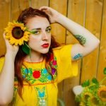 Holly Classius standing against brown fence wearing yellow shirt with red and green flowers, holding a sunflower to her ear