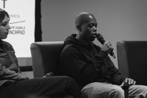 Ajain Charles sitting on chair speaking into microphone, black & white