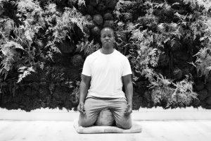 Ajani Charles kneeling on meditation mat, eyes closed. Black & white