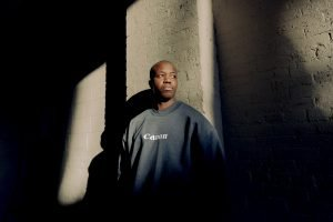 Ajani Charles in navy Canon sweater standing against wall, looking off to right